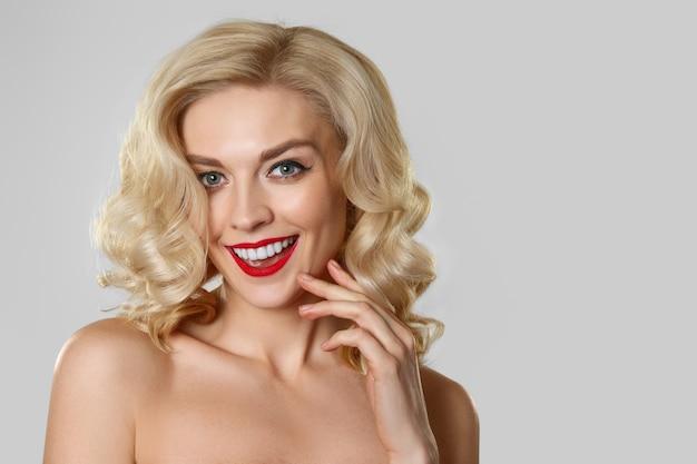 Jolie blonde aux cheveux ondulés, maquillage pour les yeux de chat et les lèvres rouges Photo Premium