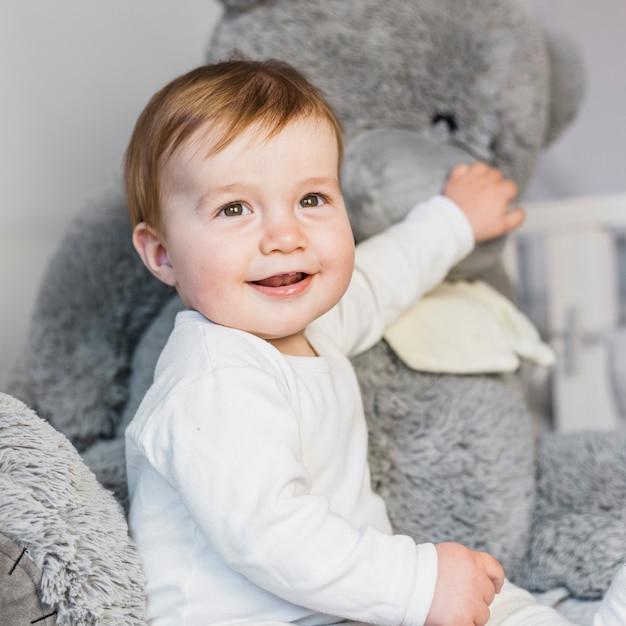 Jolie blonde bébé dans un lit blanc avec ours en peluche Photo gratuit