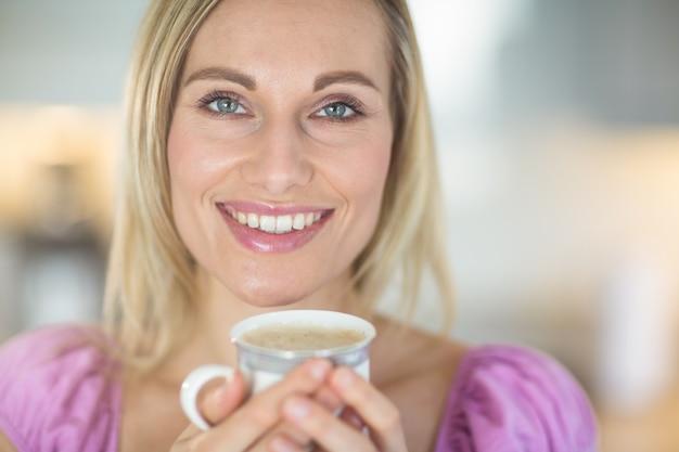Jolie blonde femme prenant un café Photo Premium