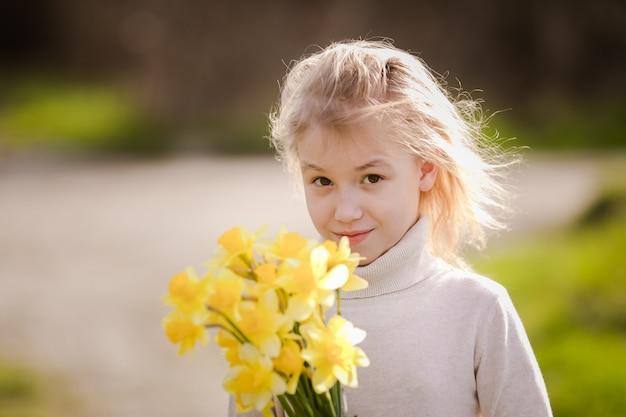Jolie blonde heureuse petite fille avec des jonquilles jaunes au pays du printemps Photo Premium