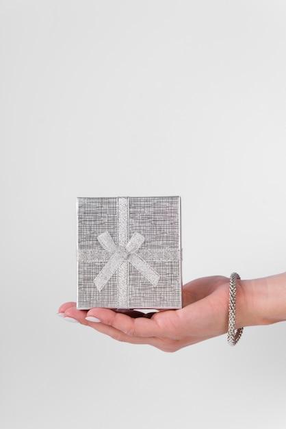 Jolie boîte cadeau en argent tenue en main Photo gratuit