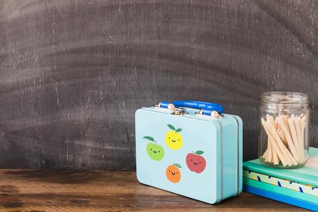 Jolie boîte à lunch près de crayons et bloc-notes Photo gratuit