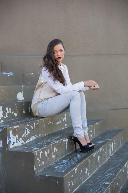 Jolie brune assise dans les escaliers Photo Premium