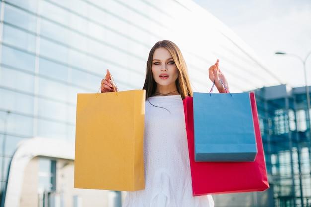 Jolie brune aux cheveux longs se tient avec des sacs à provisions devant un bâtiment de verre moderne Photo gratuit
