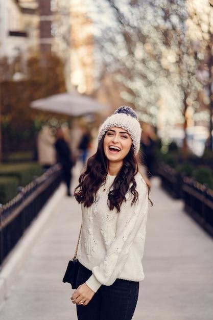 Jolie brune dans un pull blanc dans une ville Photo gratuit