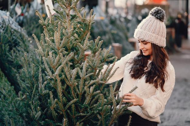 Jolie brune dans un pull blanc avec sapin de noël Photo gratuit