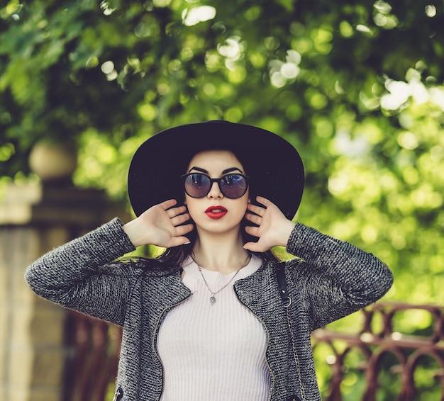 Jolie brune avec des lèvres rouges au chapeau et des lunettes de soleil posant dans la ville Photo Premium