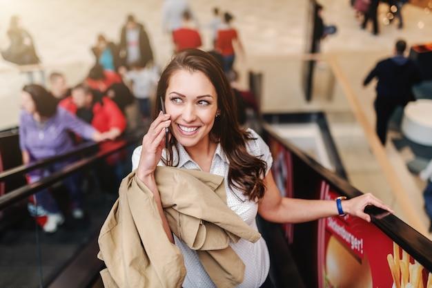 Jolie Brune Souriante Tenant Une Veste Et Utilisant Un Téléphone Intelligent Tout En Montant L'escalator Dans Le Centre Commercial. Photo Premium
