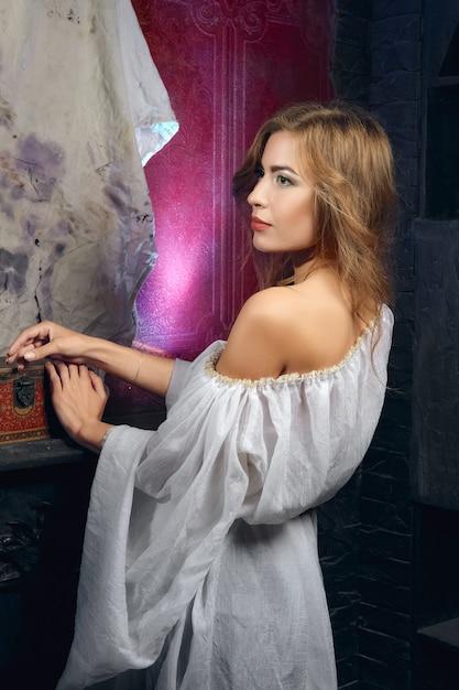 Jolie dame mystique en robe blanche gothique dans un cachot souterrain Photo Premium