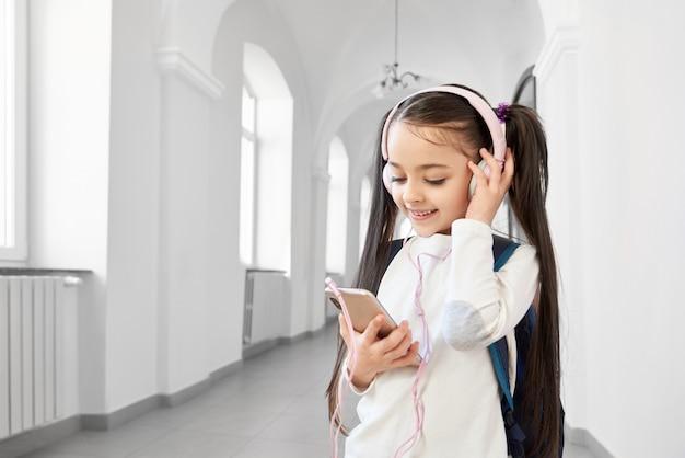 Jolie, drôle écolière en sweat-shirt blanc avec un casque tenant un téléphone rose. Photo Premium
