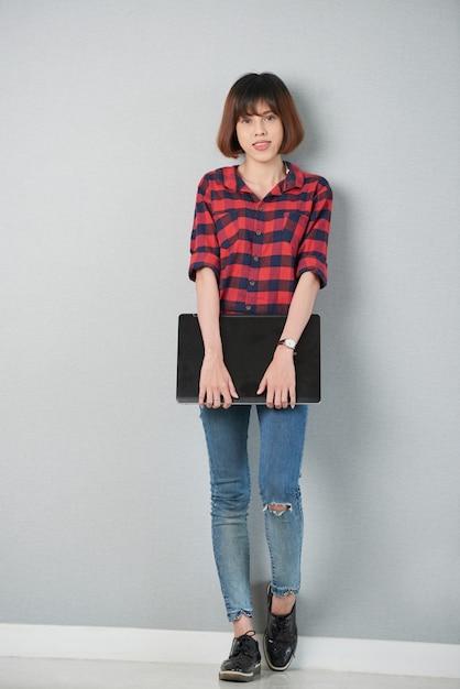 Jolie étudiante tenant le portable debout devant le mur gris Photo gratuit