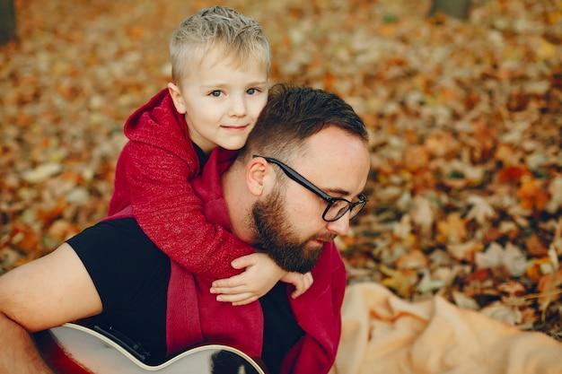 Jolie famille jouant dans un parc en automne Photo gratuit