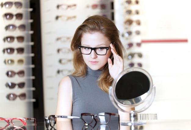 Jolie femme acheter de nouvelles lunettes Photo Premium