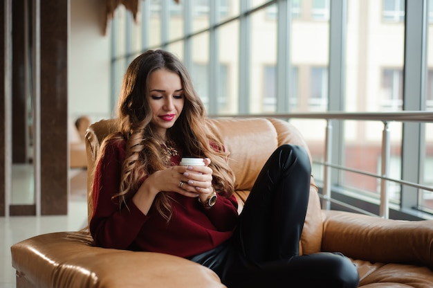 Jolie femme d'affaires dans un pull rouge prendre une pause-café Photo Premium