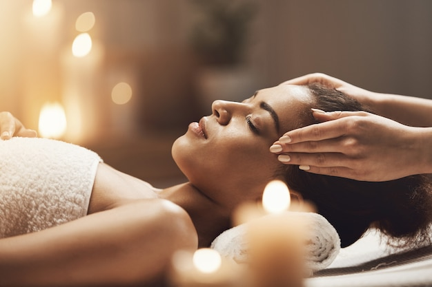 Jolie Femme Africaine Bénéficiant D'un Massage Du Visage Dans Le Salon Spa. Photo gratuit