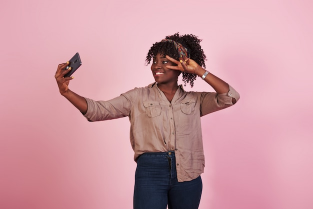 Jolie Femme Afro-américaine Dans Des Vêtements Décontractés Prend Selfie Et Montre Le Geste Avec Deux Doigts Sur Fond Rose En Studio Photo gratuit