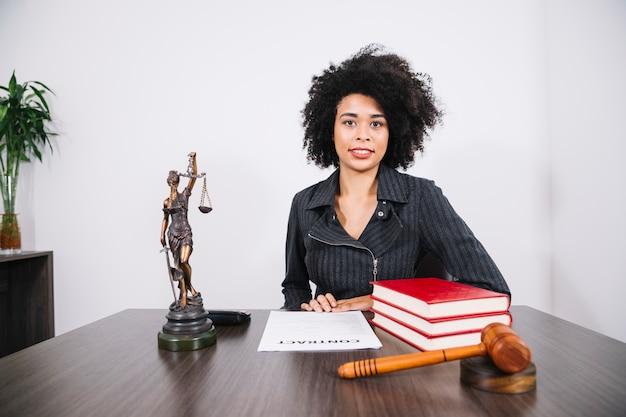 Jolie femme afro-américaine à table avec des livres, document et figure Photo gratuit