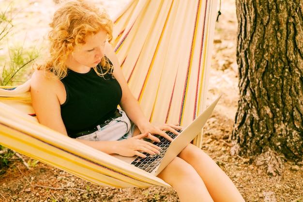 Jolie femme à l'aide d'un ordinateur portable dans un hamac Photo gratuit