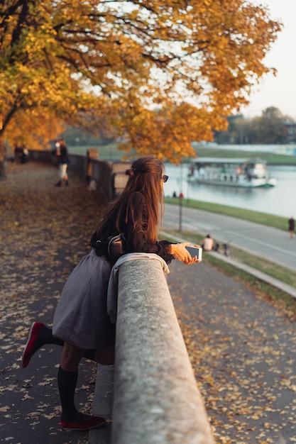 Jolie femme à l'aide de smartphone en plein air dans le parc Photo gratuit