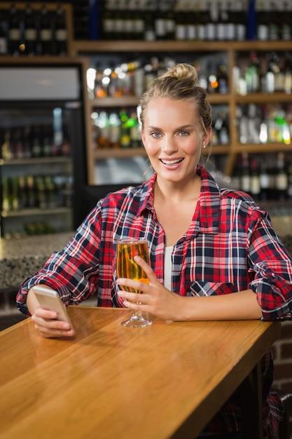 Jolie femme à l'aide de smartphone et prendre une bière Photo Premium