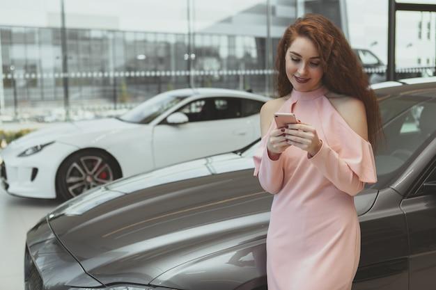 Jolie femme à l'aide d'un téléphone intelligent chez un concessionnaire automobile Photo Premium