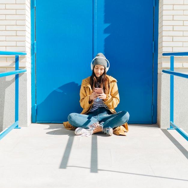 Jolie femme à l'aide de téléphone portable portant casque assis contre la porte bleue Photo gratuit
