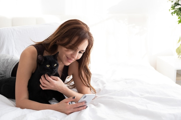 Jolie Femme à L'aide De Téléphone Avec Son Chat Noir, Portant Ensemble Dans La Chambre Blanche Photo Premium
