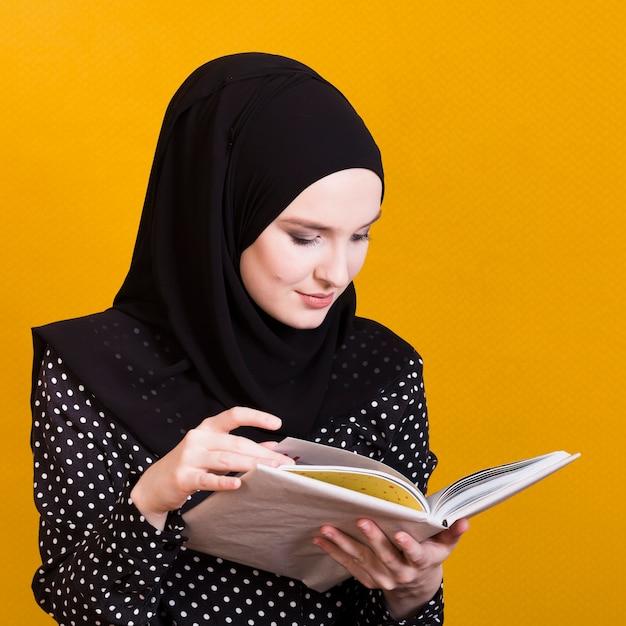 Jolie femme arabe, lecture de manuel sur fond jaune vif Photo gratuit