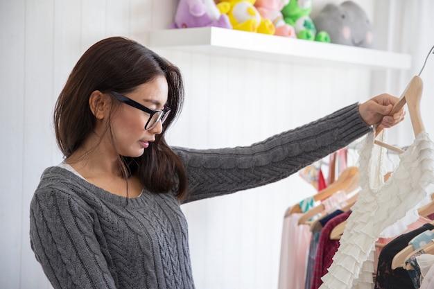 Jolie femme asiatique choisissant des vêtements et essayant des vêtements de mode avec miroir à la maison Photo Premium