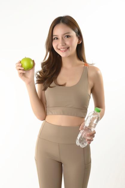 Jolie femme asiatique avec pomme et eau Photo Premium