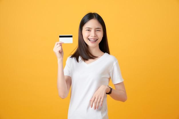 Jolie Femme Asiatique Souriante Tenant Le Paiement Par Carte De Crédit Sur Le Mur Jaune Photo Premium