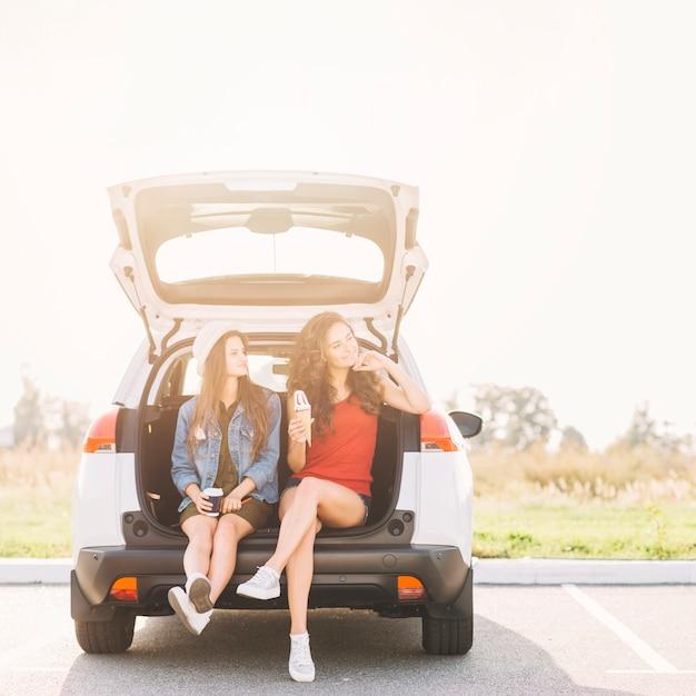 Jolie femme assise sur le coffre de la voiture Photo gratuit