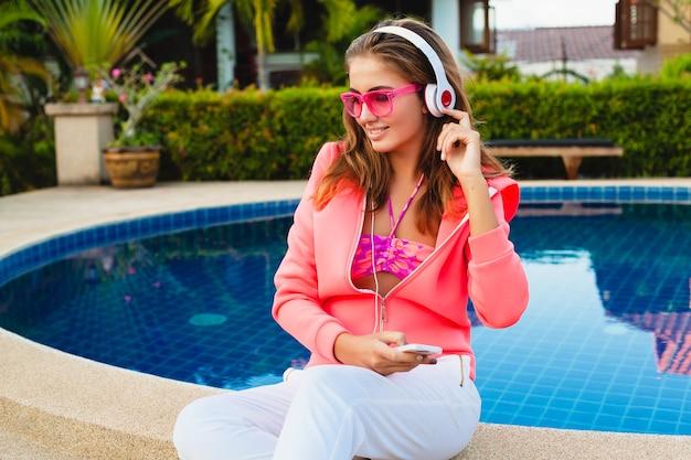 Jolie Femme Assise à La Piscine En Sweat à Capuche Rose Coloré Portant Des Lunettes De Soleil, écouter De La Musique Dans Les écouteurs En Vacances D'été, Style Sport Photo gratuit