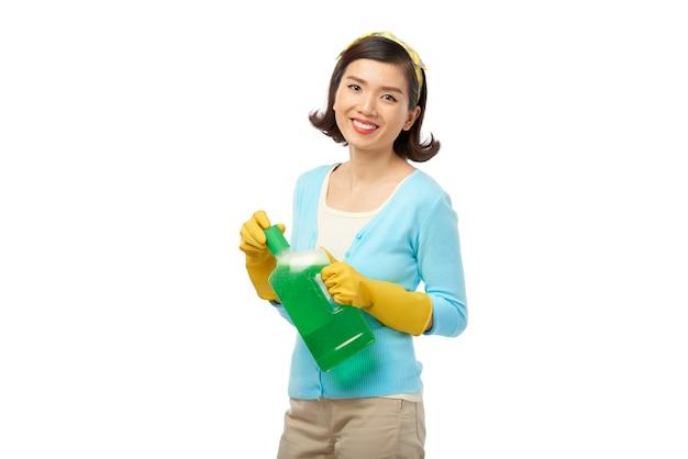 Jolie femme au foyer avec bouteille de détergent Photo gratuit