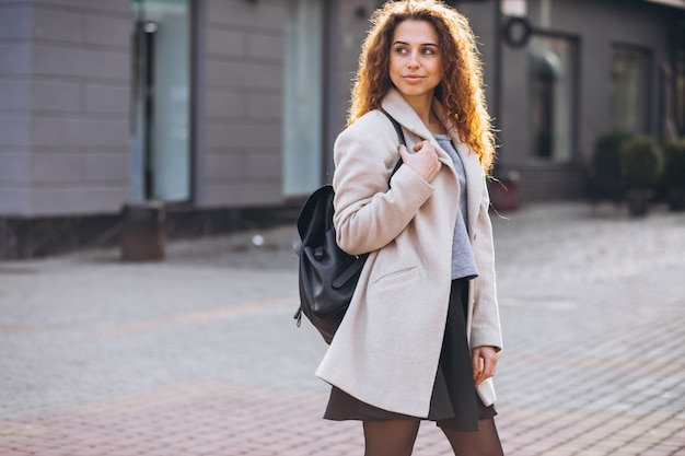 Jolie femme aux cheveux bouclés, marchant dans un manteau d'automne Photo gratuit