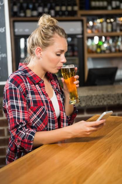Jolie femme ayant une bière et regardant un smartphone Photo Premium