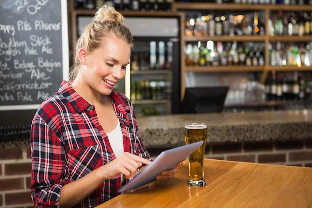 Jolie femme ayant une bière et regardant une tablette Photo Premium