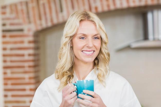 Jolie femme ayant une tasse de café dans la cuisine Photo Premium