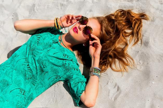 Jolie Femme Blonde Allongée Sur La Plage Tropicale Ensoleillée, Portant Des Lunettes De Soleil élégantes Et Cool, Une Tunique Boho Couleur Et Des Accessoires à La Mode Lumineux Photo gratuit