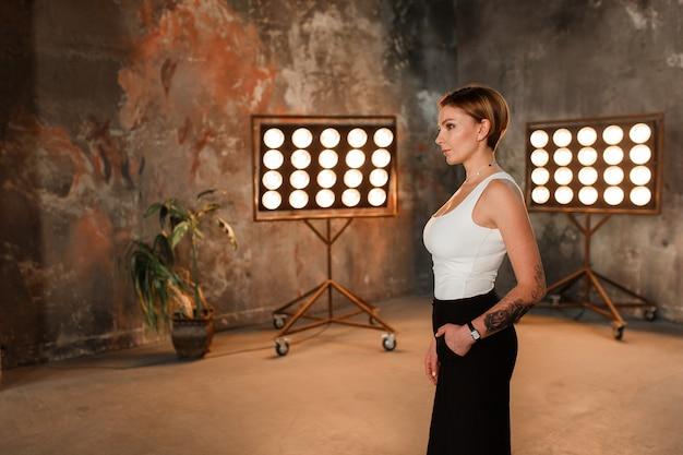 Une jolie femme brune dans une décoration de chambre loft avec support de lampe rétro Photo gratuit
