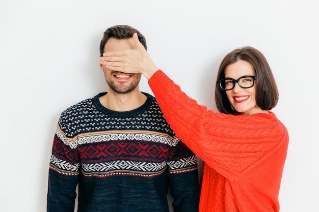 Jolie femme brune avec une expression positive, couvre les yeux de l'homme, porte des chandails d'hiver Photo Premium
