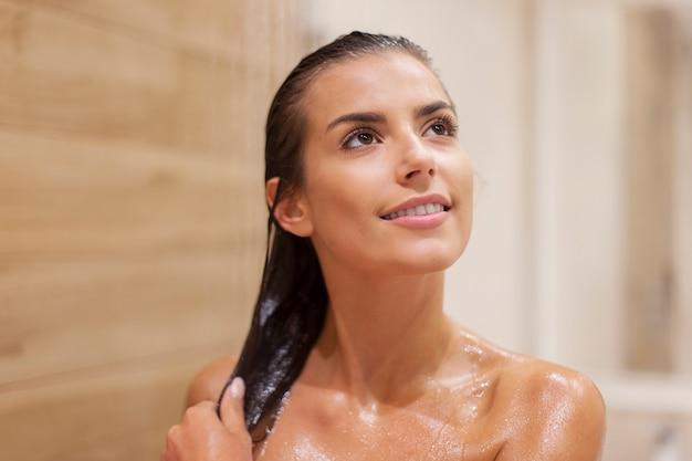 Jolie Femme Brune Prenant Une Douche Photo gratuit