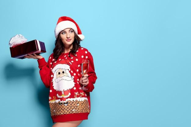 Jolie femme brune en pull rouge avec le père noël, coupe de champagne sur fond bleu Photo Premium