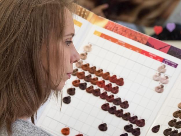 Une Jolie Femme Choisit Une Teinture Pour Les Cheveux. Le Choix Des Couleurs De Teinture Capillaire. Palette De Couleurs. Photo Premium