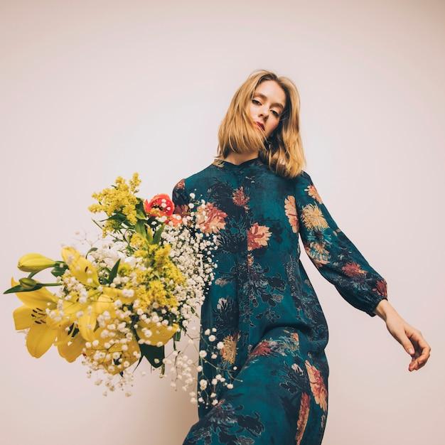 Jolie femme confiante en robe avec bouquet de fleurs fraîches Photo gratuit