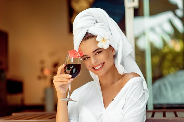 Jolie femme dans un peignoir blanc et une serviette tenant un verre à vin et souriant à la caméra Photo Premium