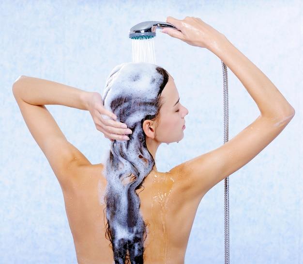 Jolie Femme Debout En Arrière Et Laver Ses Longs Cheveux Photo gratuit