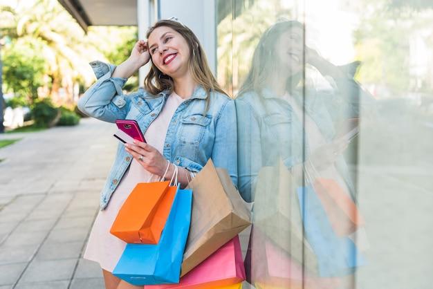 Jolie femme debout avec des sacs à provisions, smartphone et carte de crédit Photo gratuit