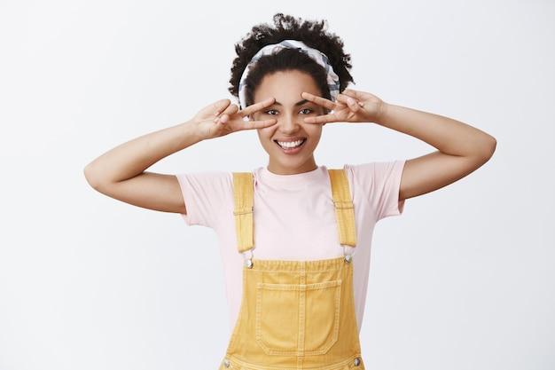 Jolie Femme élégante à La Peau Sombre En Bandeau Sur Les Cheveux Et Une Salopette à La Mode Jaune, Montrant Un Geste De Paix Sur Les Yeux Et Souriant Avec Une Expression Insouciante Et Heureuse Photo gratuit