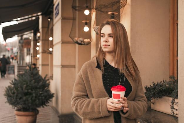 Jolie Femme élégante Porte Un Manteau Beige Chaud, Se Tient Dans La Rue Avec Une Tasse De Café Dans Ses Mains Et Regarde Sur Le Côté Fille En Vêtements De Printemps Dans La Rue De La Ville Photo Premium